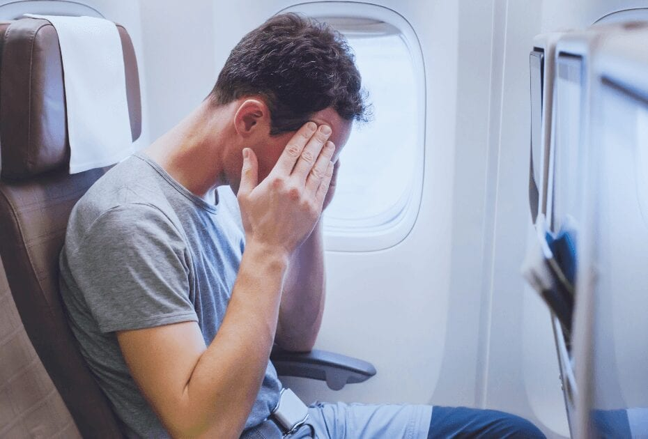 A man feeling ill on an airplane