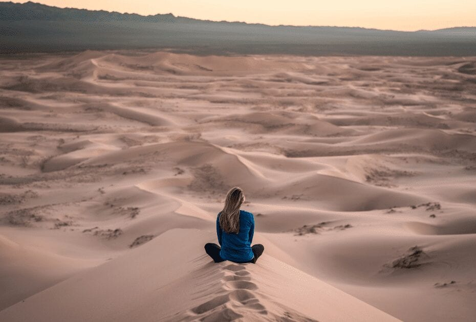 A woman sitting in the desert