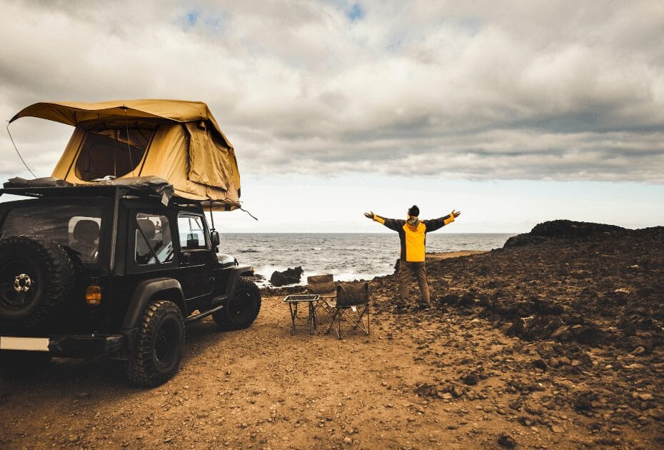 An adventurer enjoying the sea view with his off road car