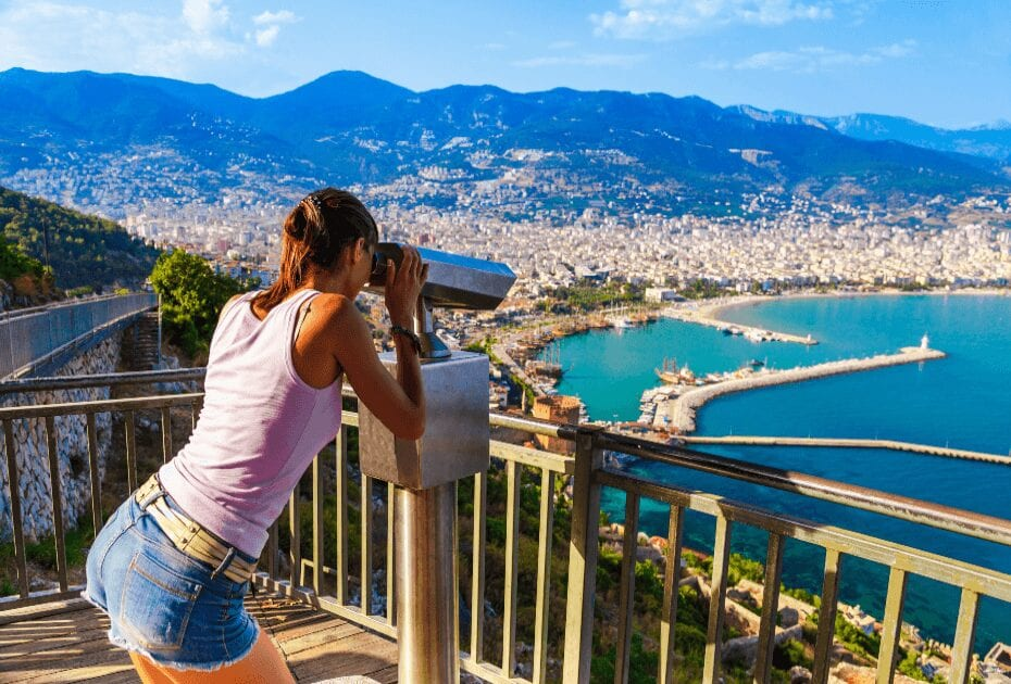 Woman looking on landscape of Alanya with telescope