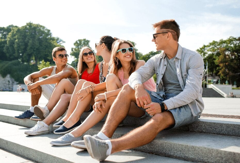 A friendship leisure summer people concept group of smiling friends sitting on city street