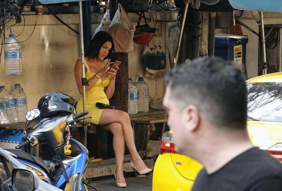 A ladyboy sitting on bench and using her phone