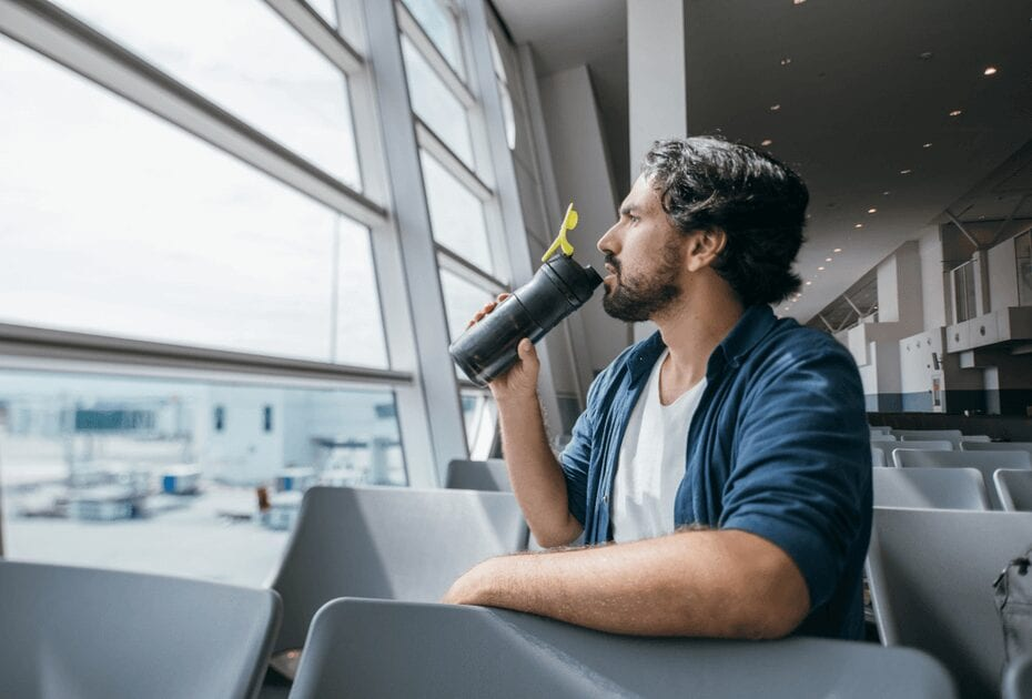 A man sits by the gate at the airport with a bottle of water in his hands. A young guy drinks water, waiting for boarding a plane near a large window overlooking the airport