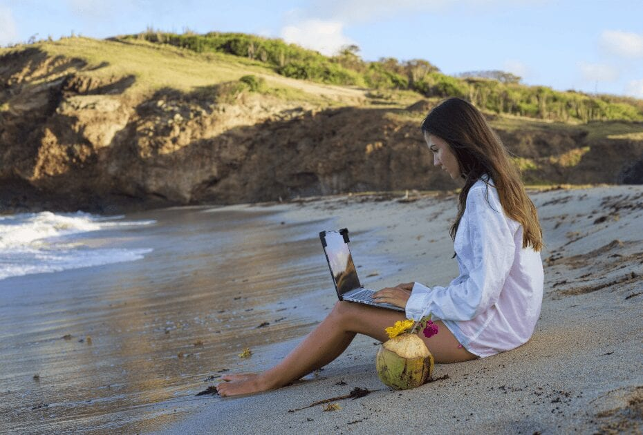 A young woman in a masculine white shirt working on her laptop on the dreamy Caribbean beach (1)