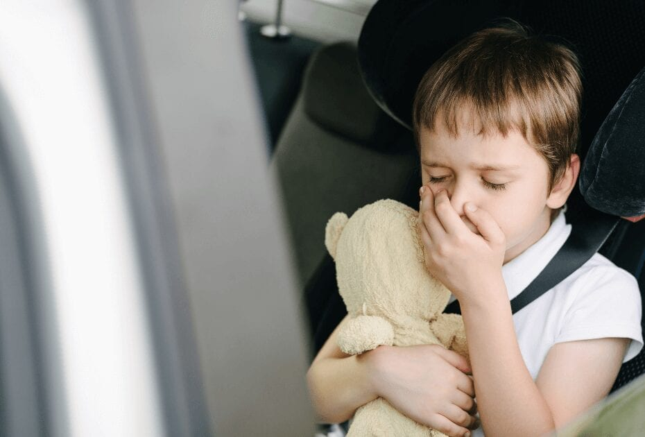 An ill child in the backseat of a car