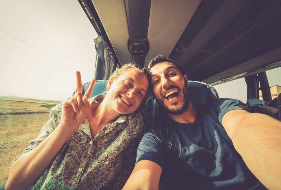 Backpackers traveling around the world on the bus. Young handsome man with his girlfriend in a traditional bus taking a selfie on a smartphone.