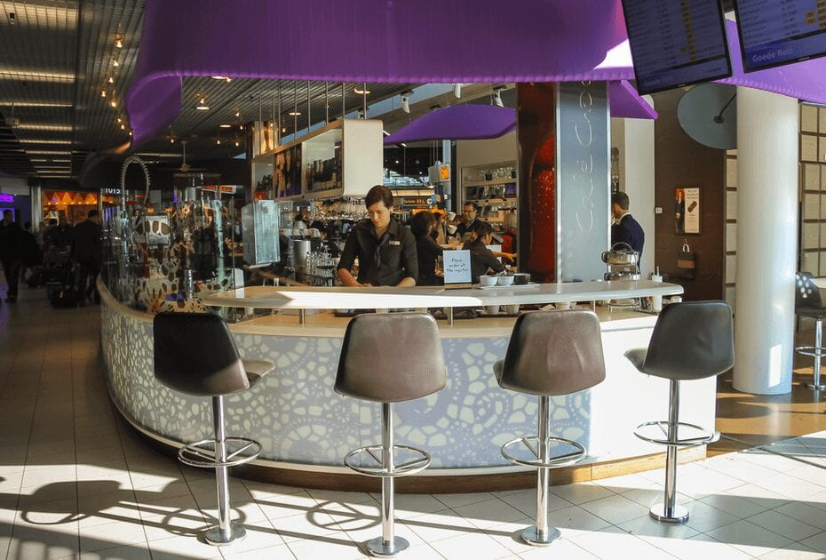Bartenders serve customers in the cafe at the airport Amsterdam Schiphol, Netherlands