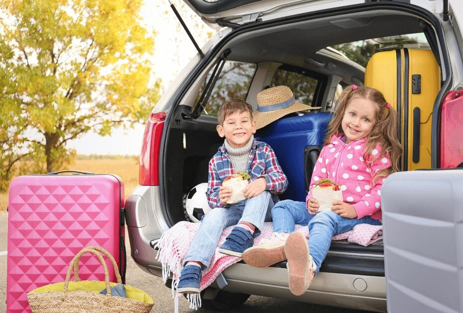 Children on read trip eating in car trunk