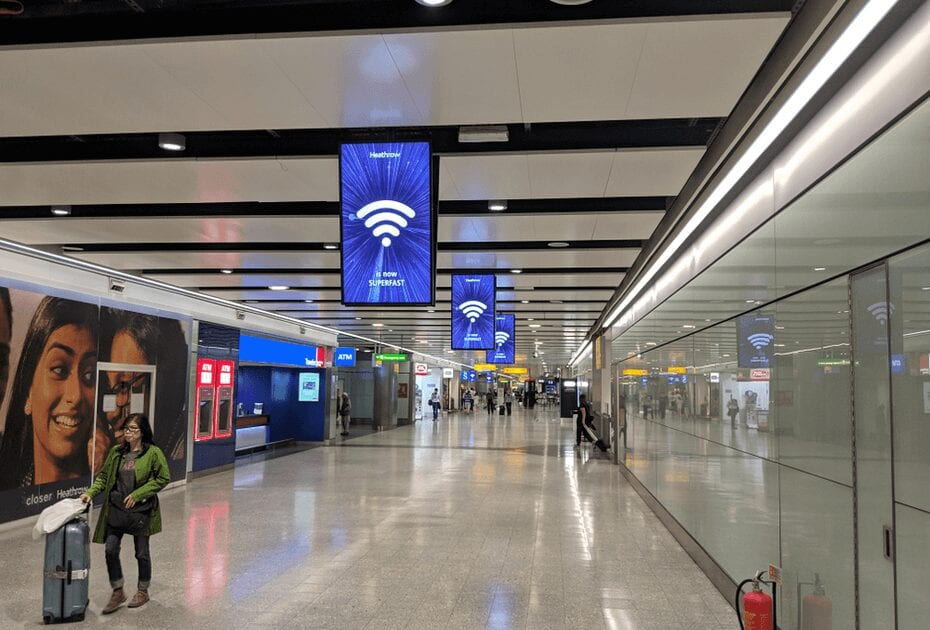 Heathrow Airport London terminal 3 with blue screen displaying WIFI sign at the departures