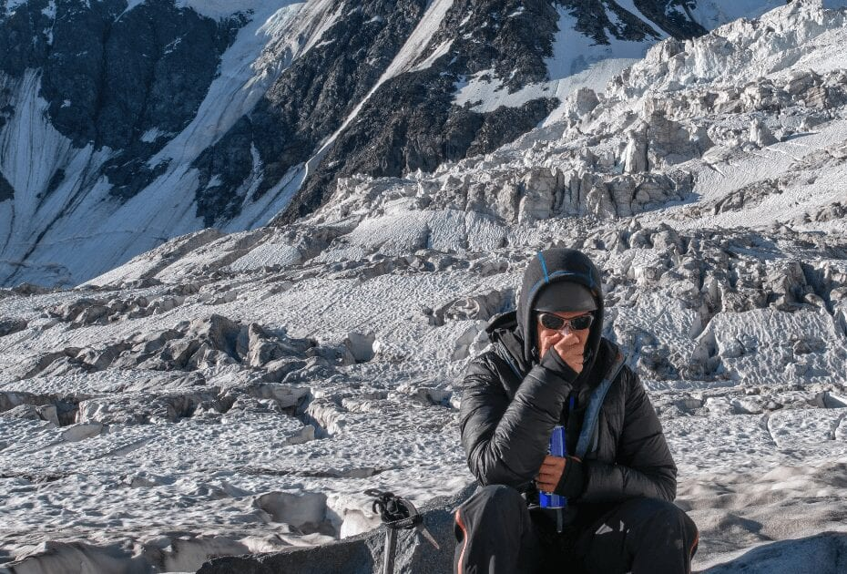 High altitude sickness. Climber breathing oxygen from the O2 tank on the background of glacier and covered with snow and ice mountains
