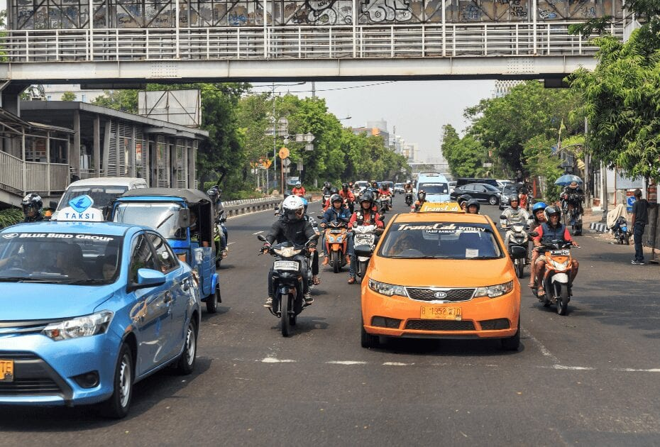 Typical view of people commuting with scooter and cab (taksi) in traffic in the streets of Jakarta, Indonesia