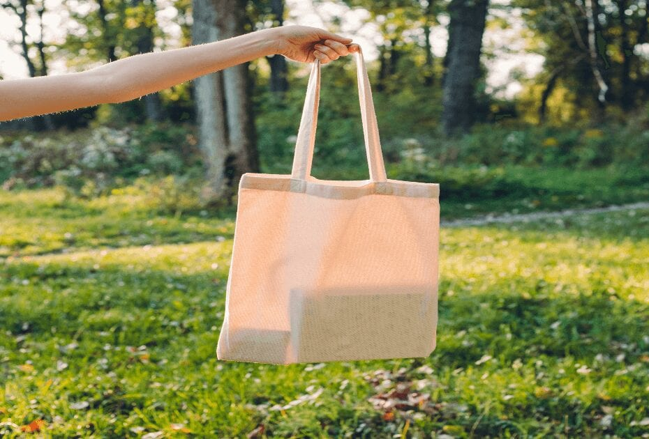 Woman holding canvas tote bag on nature background