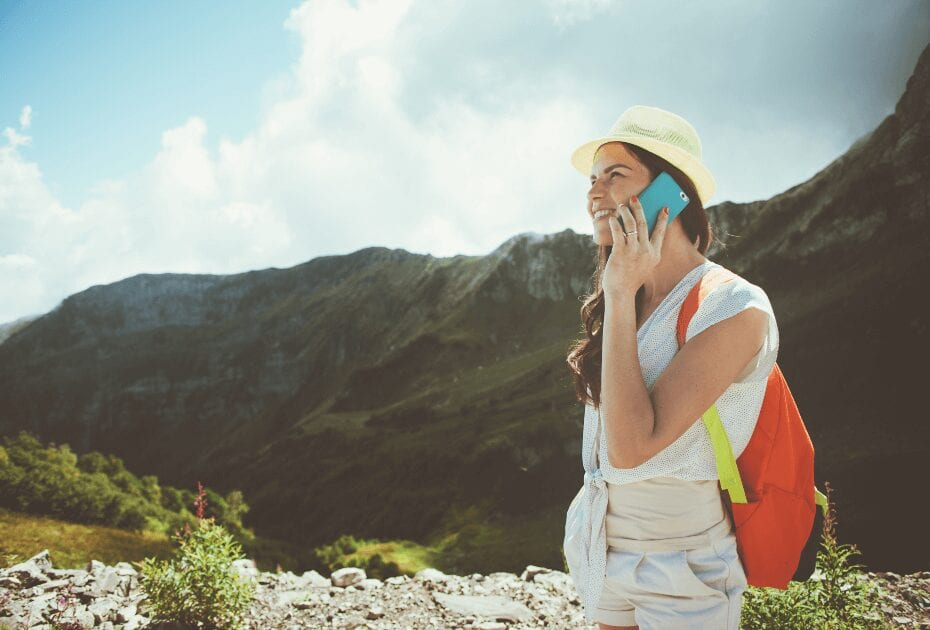cheerful woman talking on phone mountains